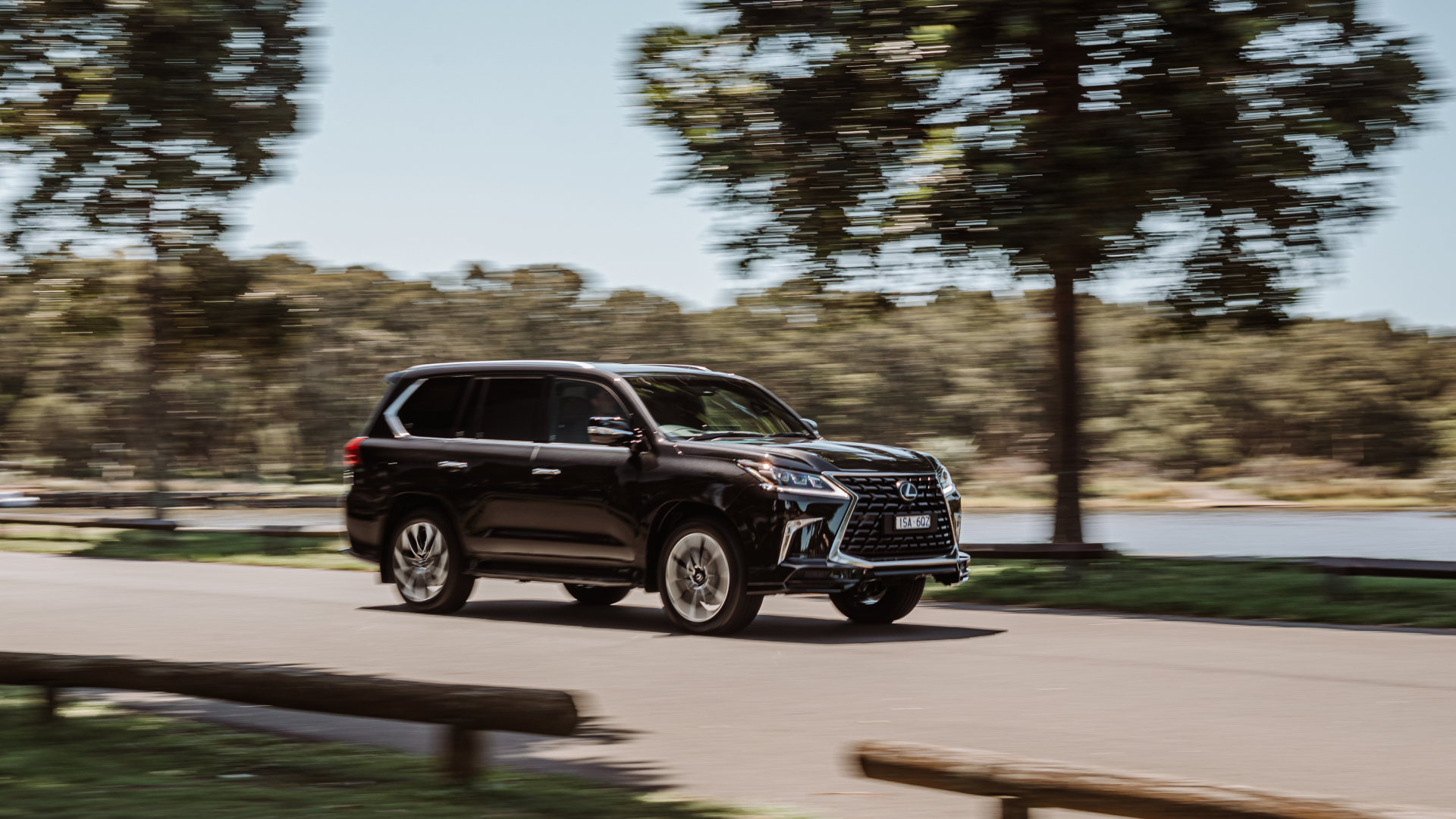 A 2021 Lexus LX 570 S drives along a road at speed.